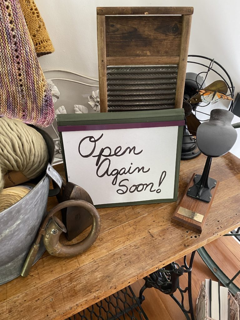 """Antique shop table with """"Open Again Soon!"""" sign"""