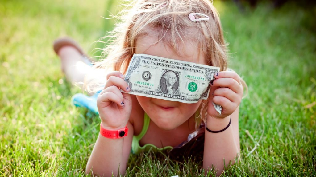 Child lying on grass hiding face behond dollar bill